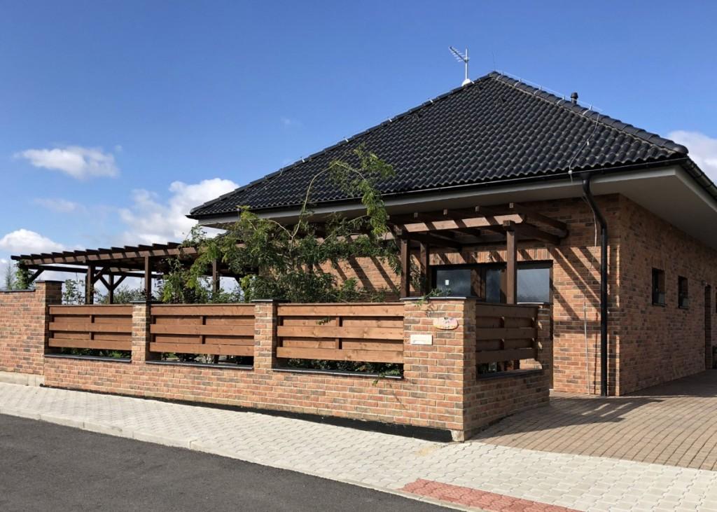 Kastanjebruin na plotě i na fasádě domu